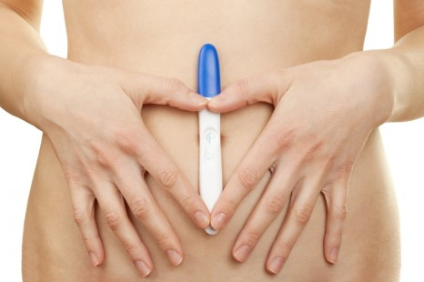 Woman holding a positive pregnancy test against white background