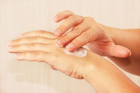Female hands using skin cream
