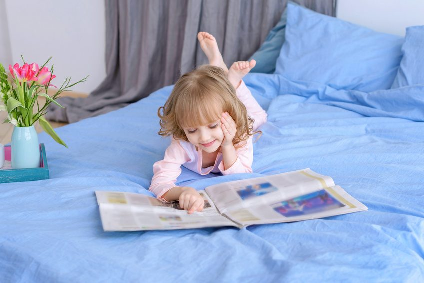 portrait of beautiful girl reading a newspaper at home/in the news/modern children